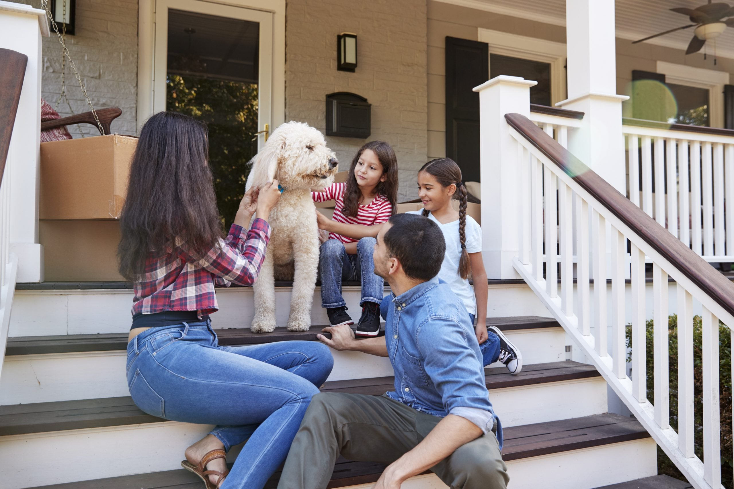 Family With Dog Sitting On Steps Of New Home On Moving In Day
